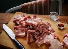Surowi wieprzowina ziobro na drewnianej tnącej desce obok kuchennego noża, soli, pikantność i ręcznika, Zdjęcia Royalty Free