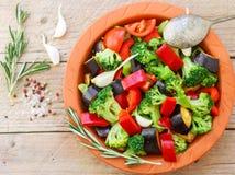 Surowi świezi warzywa - brokuły, oberżyna, dzwonkowi pieprze, pomidory, cebule, czosnek w glinianym pieczenia naczyniu Obrazy Stock