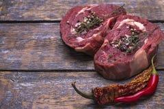 Surowi wołowina stki, przygotowywający dla piec, solą, pieprzą, na drewnianym tle Obraz Stock