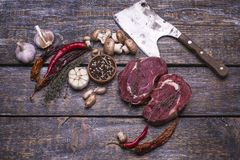 Surowi wołowina stki, przygotowywający dla piec, solą, pieprzą, pomidory, czosnek i ax na drewnianym tle, Obraz Stock