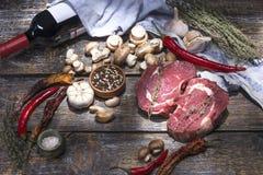Surowi wołowina stki, przygotowywający dla piec, solą, pieprzą, pomidory, czosnek na drewnianym tle Zdjęcia Royalty Free
