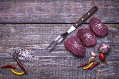 Surowi wołowina stki, przygotowywający dla piec, solą, pieprzą, pomidory, czosnek, na drewnianym tle Odgórny widok Fotografia Stock
