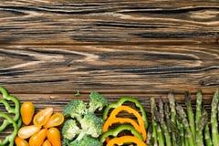 Surowi zieleni i żółci veggies Mieszkanie kłaść na drewnianym stole zdjęcia royalty free