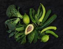 Surowi zieleni warzywa ustawiający Brokuły, avocado, pieprz, szpinak, zuccini i wapno na zmroku, drylują tło Fotografia Royalty Free