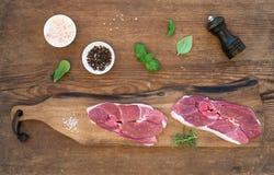 Surowy świeżego mięsa jagnięcy antrykot i seasonings na tnącej desce nad nieociosanym drewnianym tłem Obrazy Royalty Free