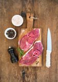 Surowy świeżego mięsa jagnięcy antrykot i seasonings na tnącej desce nad nieociosanym drewnianym tłem Obraz Royalty Free