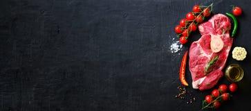 Surowy świeżego mięsa stek z czereśniowymi pomidorami, gorącym pieprzem, czosnkiem, olejem i ziele na zmroku kamieniu, betonowy t Zdjęcie Stock