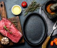 Surowy świeżego mięsa stku wołowiny tenderloin, ziele i pikantność wokoło smażyć niecka talerza, Karmowy kulinarny ackground z ko zdjęcia stock