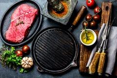 Surowy świeży marmurkowaty mięsny stek i seasonings na zmroku wykładamy marmurem tło zdjęcia stock