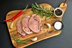 Surowy świeży uncooked pokrojony wieprzowiny mięsa polędwicowy naczynie z rozmarynami, pieprzem, czosnkiem, solą, czerwonego chil zdjęcie stock