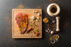 Surowy świeży wieprzowiny mięso z na pokładzie condiments na ciemnym tle Fotografia Stock