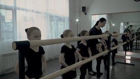 Surowy żeński nauczyciel taniec klasa uczy niektóre movenments młodego studenckiego pobliskiego baletniczego barre, ballerines ch zdjęcie wideo