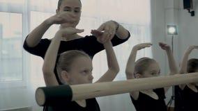 Surowy żeński nauczyciel taniec klasy poprawna pozycja małe baleriny i uczy one jak zbyt utrzymanie ręki w górę blisko zbiory