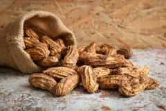 Surowy arachid w konopie worku na drewnianym tle Obrazy Stock
