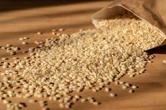 Surowy Brown Rice Na A drewnianym stole Organicznie Brown Rice Na A stole Z torbą W tle zdjęcia royalty free