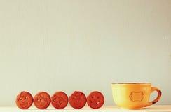 Surowy ciastka z smiley twarzą nad drewnianym stołem obok filiżanki kawy wizerunek jest retro stylem filtrującym Zdjęcia Royalty Free