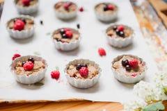 Surowy ciasto z jagodami dla babeczek rozłożonych w formy na wypiekowym papper na wypiekowa taca dekorującym ewith kwitnie Selekc obrazy stock