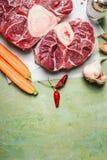 Surowy cielęcina giczoła mięso i składniki dla Osso Buco kucharstwa na nieociosanym tle, odgórny widok fotografia stock