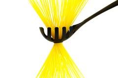 Surowy długi żółty spaghetti w czarnej łyżce odizolowywającej na bielu obrazy royalty free