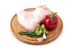 Surowy indyczy skrzydło, część kurczaka drobiowy ścierwo na drewnianej round desce z pieprzem i rozmarynami na białym tle, odizol zdjęcie royalty free