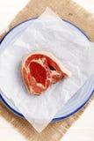 Surowy jagnięcy kotlecik z kuchnia papierem na talerzu Zdjęcie Stock