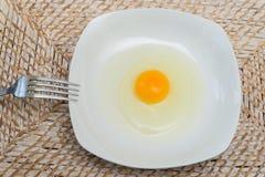 Surowy jajko na białym talerzu zdjęcie royalty free