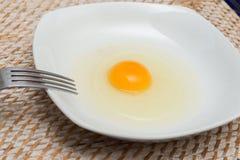 Surowy jajko na białym talerzu obraz stock