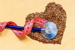 Surowy lnów ziaren serce kształtujący i stetoskop Zdjęcia Royalty Free