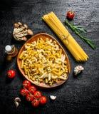 Surowy makaronu asortyment z rozmarynami, pomidorami i pieczarkami, obraz royalty free
