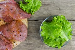 Surowy mięso z pikantność i sałatką opuszcza w szklanym pucharze na starego rocznika drewnianym tle Odgórny widok obrazy stock