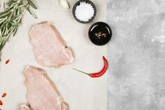 Surowy mięso z różnorodnymi pikantność na szarym tle Odgórny widok, policjant Zdjęcia Stock