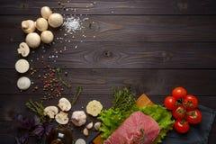 Surowy mięso z składnikami na drewnianym tle obraz royalty free
