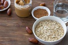 Surowy oatmeal w białym pucharze, dat owoc, maśle orzechowym, kakao i szkle woda, składniki dla wyśmienicie zdrowego śniadania zdjęcie stock