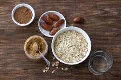 Surowy oatmeal w białym pucharze, maśle orzechowym, dat owoc, kakao i szkle woda, składniki dla wyśmienicie czekoladowej owsianki zdjęcia stock