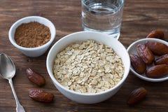 Surowy oatmeal w bia?ym pucharze, dat owoc, kakao i szkle woda, sk?adniki dla wy?mienicie zdrowego ?niadania fotografia royalty free