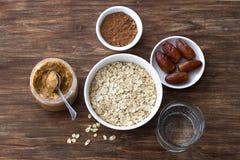 Surowy oatmeal w bia?ym pucharze, ma?le orzechowym, dat owoc, kakao i szkle woda, sk?adniki dla wy?mienicie czekoladowej owsianki zdjęcie royalty free