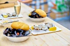 Surowy owoce morza - mussels, ostrygi na drewnianym stole z szkłem Fotografia Royalty Free
