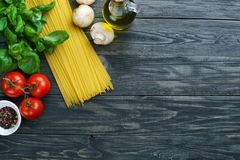 Surowy spaghetti, pomidory, basil, oliwa z oliwek, pieczarki i pikantność, obraz royalty free