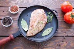 Surowy stek od kurczaka polędwicowego na żelaznej czarnej smaży niecce z ziele, pikantność, laurowy liść i gałąź tymiankowy pobli obraz stock