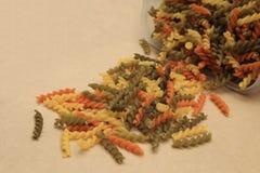 Surowy trzy kolorów skręta ślimakowaty makaron rozpraszał na brown sklejkowym tle Zdjęcie Stock