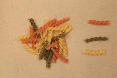 Surowy trzy kolorów skręta ślimakowaty makaron rozpraszał na brown sklejkowym tle Zdjęcia Royalty Free