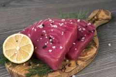 Surowy tuńczyk polędwicowy z koperem, cytryną i pieprzami w oliwnej tnącej desce, Obraz Royalty Free