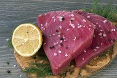 Surowy tuńczyk polędwicowy z koperem, cytryną i pieprzami w oliwnej tnącej desce, Zdjęcia Royalty Free