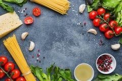 Surowy Włoski makaronu spaghetti i kulinarne składników czereśniowych pomidorów sera zielenie Włoski karmowy zmroku kamienia tło  zdjęcie stock