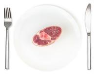 Surowy wieprzowina knykieć na talerzu z rozwidleniem i nożu odizolowywającym Zdjęcia Royalty Free