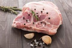 Surowy wieprzowina kotlecika stek i czosnek, pieprz na drewnianym tle Obraz Stock