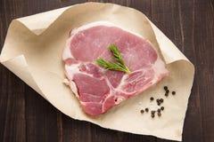 surowy wieprzowina kotlecika stek na papierowym i drewnianym tle Zdjęcia Royalty Free