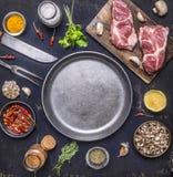 Surowy wieprzowina stek z ziele, pieczarkami i czosnkiem wokoło niecki miejsca dla teksta, rama na drewnianego nieociosanego tła  Obraz Royalty Free