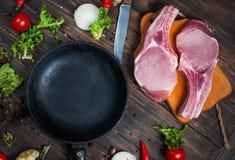 Surowy wieprzowina stek z ziele, pieprzem i czosnkiem wokoło niecki miejsca dla teksta, rama na drewnianego nieociosanego tła odg Zdjęcie Royalty Free