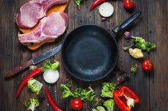 Surowy wieprzowina stek z ziele, pieprzem i czosnkiem wokoło niecki miejsca dla teksta, rama na drewnianego nieociosanego tła odg Obrazy Stock